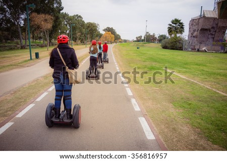 Group of people traveling on Segway in the park - stock photo