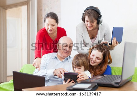 Group of people  uses few various electronic devices in home interior   - stock photo