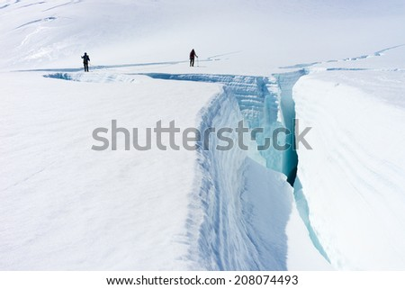 Group of people walking among snows of New Zealand Alps - stock photo