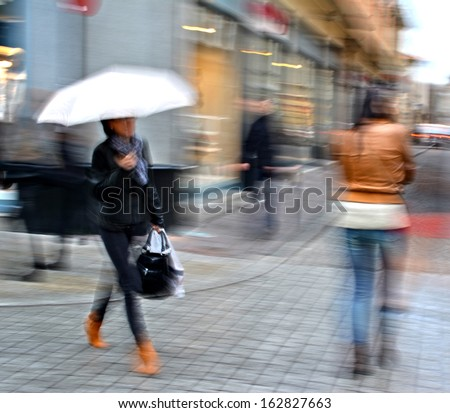 Group of  people walking down the street in motion blur - stock photo