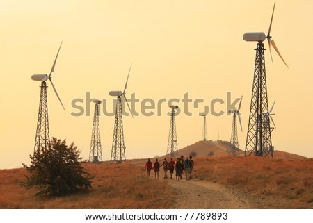 Group of people walking through fields with wind generators - stock photo