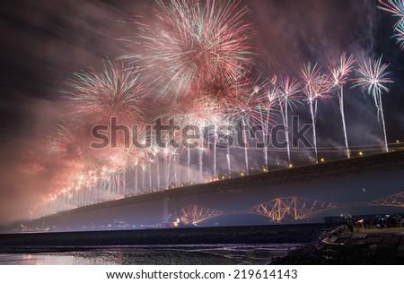 Group of people watching fireworks over Forth road bridge, Edinburgh, Scotland, UK  - stock photo