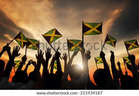 Group of People Waving Flag of Jamaica in Back Lit - stock photo