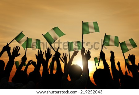 Group of People Waving Flag of Nigeria in Back Lit - stock photo