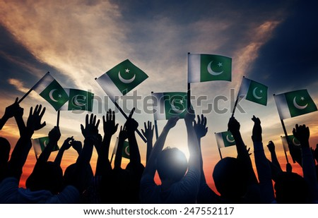Group of People Waving Flag of Pakistan in Back Lit - stock photo