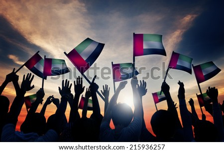 Group of People Waving Flag of UAE in Back Lit - stock photo