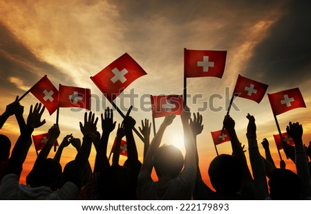 Group of People Waving Switzerland Flags in Back Lit - stock photo