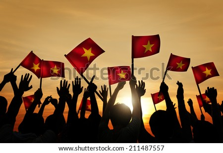 Group of People Waving Vietnamese Flags in Back Lit - stock photo