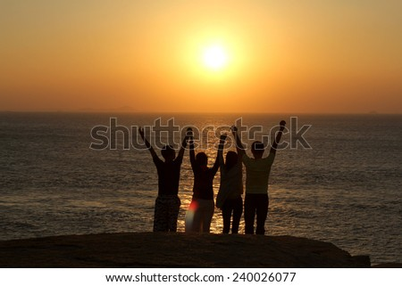 Group of People with Raised Arms looking at Sunset - stock photo