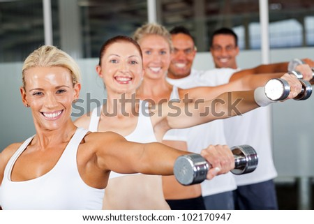 group of people working out with dumbbells in gym - stock photo
