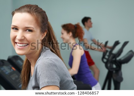 Group of people working out with happy woman in front - stock photo