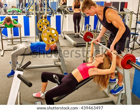 Group of people working with barbell at gym. Man back up woman lifting barbell in sport gym. - stock photo