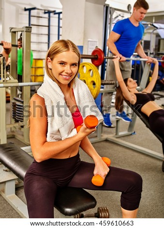 Group of people working with dumbbells his body at gym. Girl with dumbbells in hands into sport gym. - stock photo
