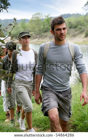 Group of persons having a walk at a lakeside - stock photo