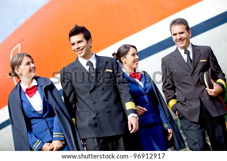 Group of pilots and flight attendants geting off an airplane - stock photo