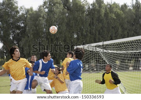 Group of players playing soccer on field - stock photo