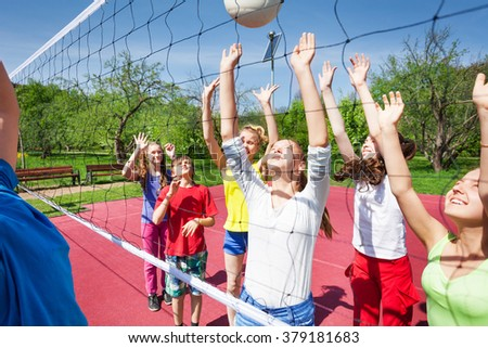 Group of playing teens with arms up jump near net - stock photo