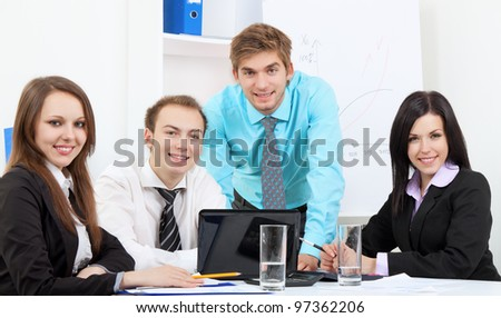 group of positive happy smile young business people at desk office, businesspeople meeting looking at camera, concept of team, working together - stock photo