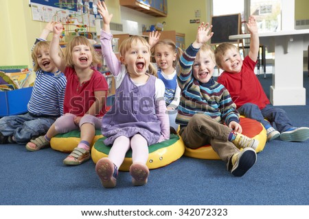 Group Of Pre School Children Answering Question In Classroom - stock photo