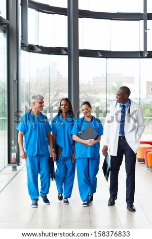 group of professional health care workers walking in hospital - stock photo