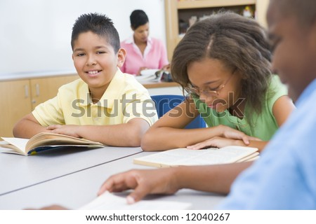 Group of pupils reading books whilst sitting at desk - stock photo