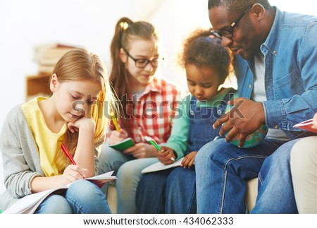 Group of pupils sitting with their teacher and making notes in exercise books - stock photo