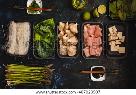 Group of raw ingredients for asian ramen soup. Noodles, chicken breast,  spring onion, tofu cheese, mushrooms, broth bowl, kale leaves in packaging tray with chopstick and black sesame seeds. - stock photo