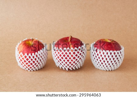 group of red apples with protective packaging on paper backgrounds - stock photo