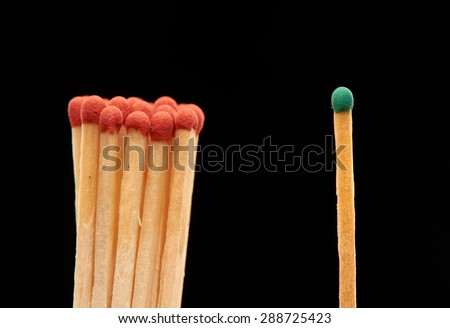Group of red wooden matches standing with green match, isolated on black background - stock photo