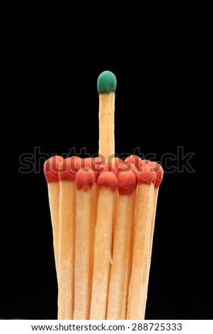 Group of red wooden matches with green match in the centre, isolated on black background - stock photo