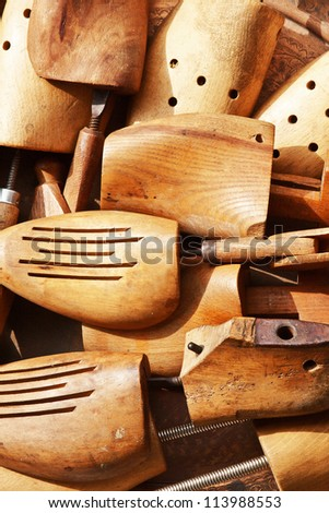 Group of retro style, old wooden shoe pads and stretchers on a flea market table. Useful for background. - stock photo