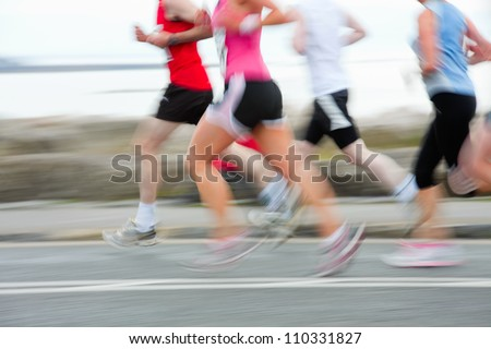 group of runners compete in the race, blurred motion - stock photo