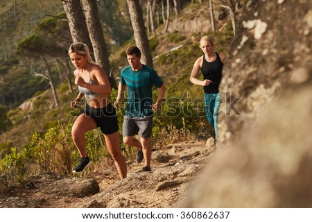 Group of runners running on rocks up a hill. Young people running cross country. - stock photo