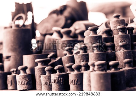 Group of rusty vintage weights. Selective focus. Low depth of field. Black and white photography. Sepia. Cream tone. - stock photo
