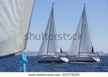 Group of sail yachts in regatta near a coast. - stock photo