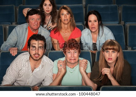Group of scared people watching movie in a theater - stock photo