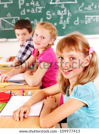 Group of school child sitting on desk in classroom. - stock photo