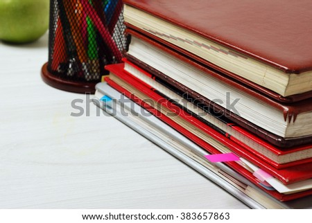 Group of school supplies, books, diaries, on a wooden table surface - stock photo