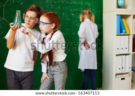 Group of schoolchildren working at chemistry lesson - stock photo