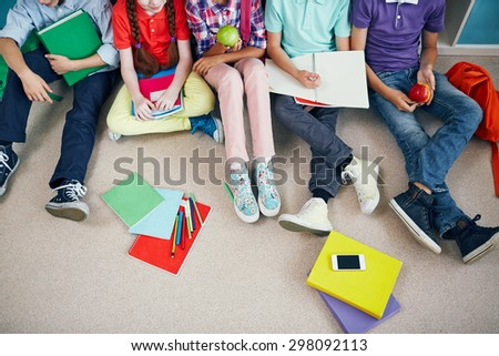 Group of schoolmates in casualwear sitting on the floor - stock photo
