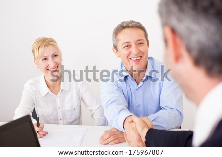 Group of senior business people working in the office on laptop and congratulating office co-worker on job well done  - stock photo