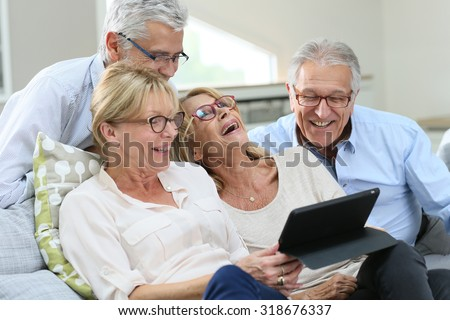 Group of senior friends with eyeglasses using digital tablet - stock photo