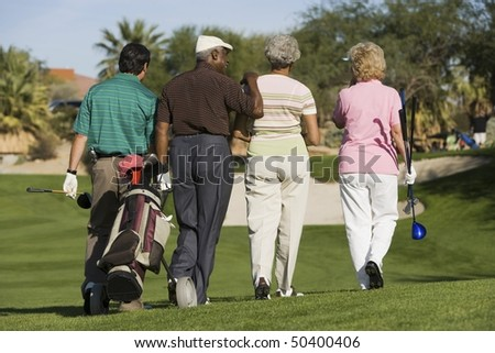 Group of senior golfers walking on golf course, back view - stock photo