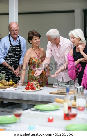 Group of senior men and women smiling standing around a table - stock photo