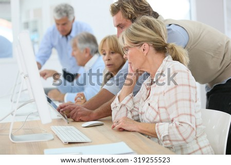 Group of senior people attending computing class - stock photo