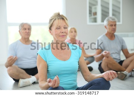 Group of senior people doing yoga exercises - stock photo