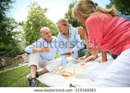 Group of senior people enjoying picnic on sunny day - stock photo
