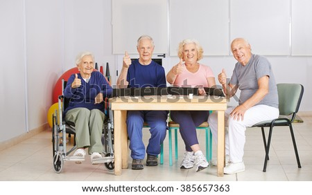 Group of senior people holding thumbs up and playing a game in nursing home - stock photo