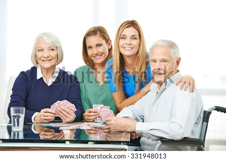 Group of senior people playing cards in nursing home with geriatric nurse - stock photo