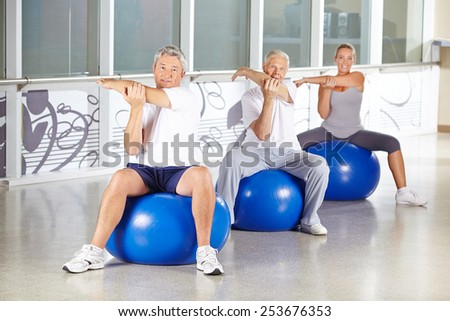 Group of senior people stretching in gym and sitting on exercise balls - stock photo